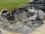 Rocks (most excavated from our acreage) are added and skimmer is set.